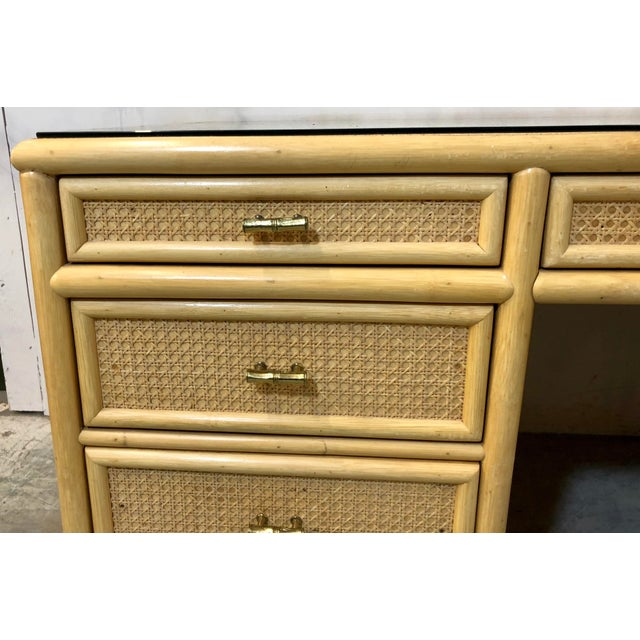 1970s rattan and faux bamboo desk with original brass faux bamboo pulls. It has one file drawer, and the remainder are...