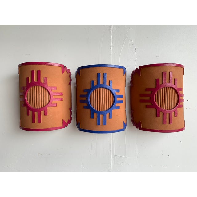 Trio of Southwestern terra cotta wall sconce covers. Cylindrical shape open on top and bottom. Sun and border detail...