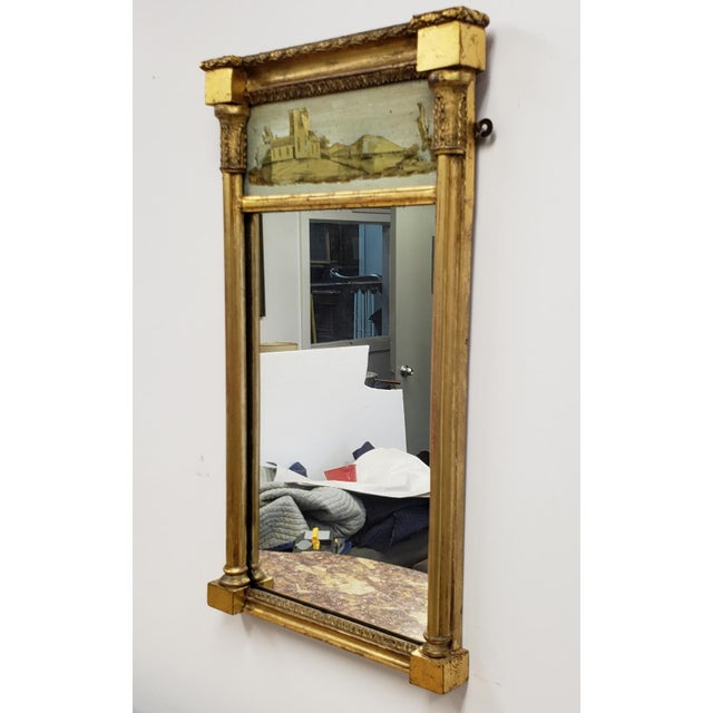Description: Antique Federal giltwood reverse painted Eglomise hanging wall mirror. Early to mid 19th Century. Restored a...