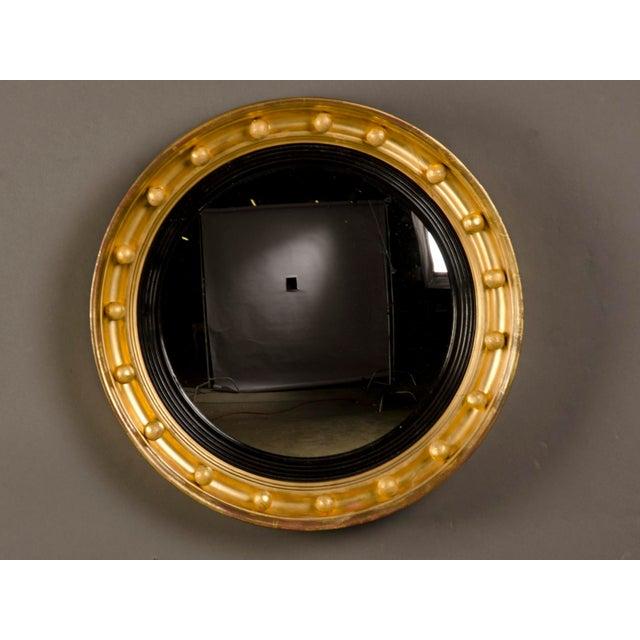 An English Regency period gold leaf circular frame circa 1825 enclosing the original convex mirror glass. This type of...