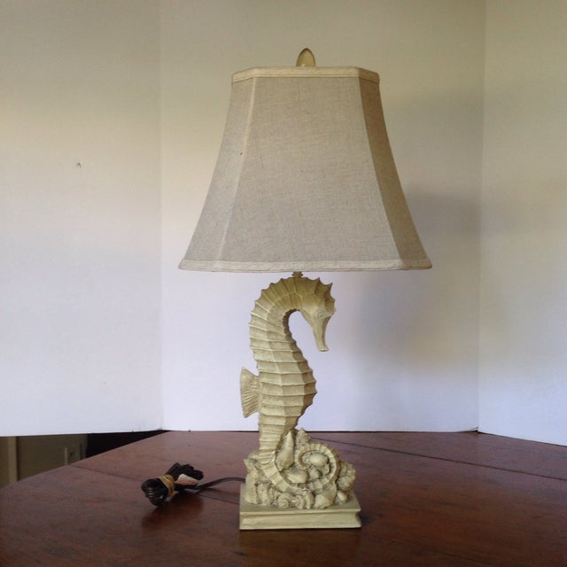 A vintage table lamp with a base of a seahorse on a mound of seashells. The base is a cream color with an oatmeal colored,...