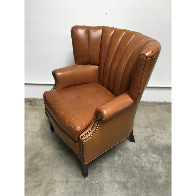 Unique and unusual early 20th century wing chair. Recently redone in a gorgeous tan mahogany leather (front channel tufts...