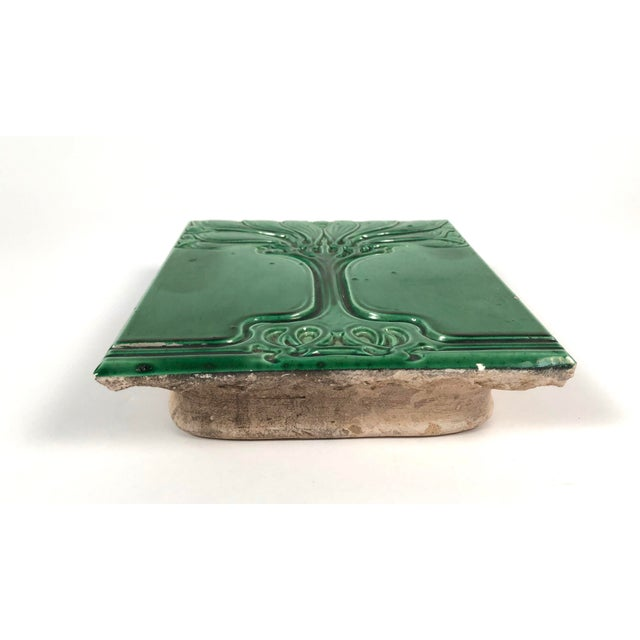 A beautiful Art Nouveau period emerald green glazed ceramic tile decorated with a wonderfully graphic, sinuous, stylized...