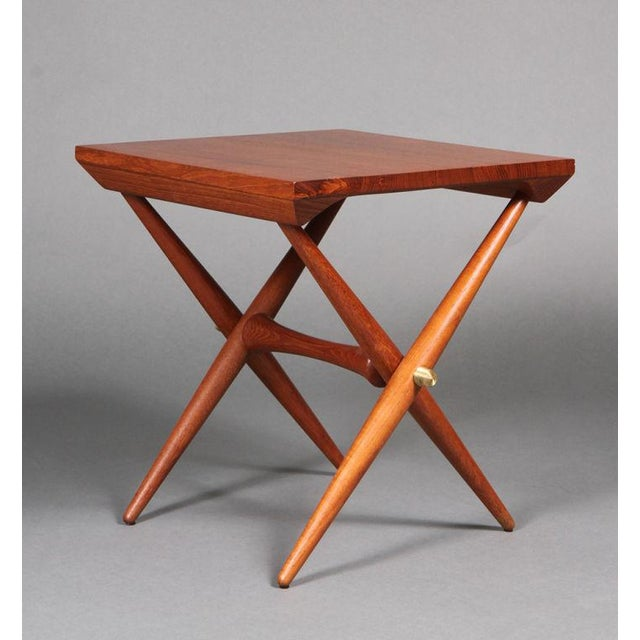 A pair of trestle base occasional tables with staved teak tops, finely turned teak legs and stretcher and ribbed brass...