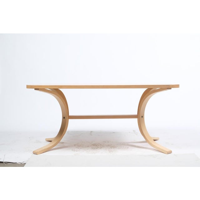 Asko mid-Century Modern-style birch cocktail/coffee table featuring a natural finish and four bent wood legs. Asko is...