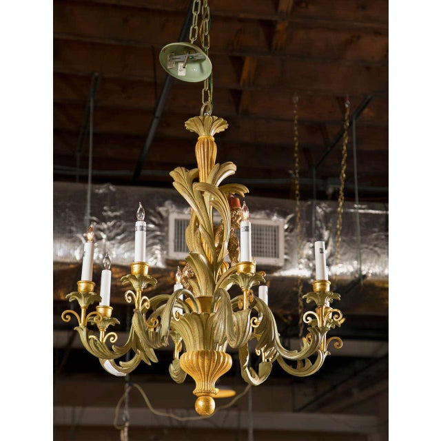A sensational, French, 8-arm chandelier crafted of wood and painted in green and parcel-gilt. Decorated with all-over...
