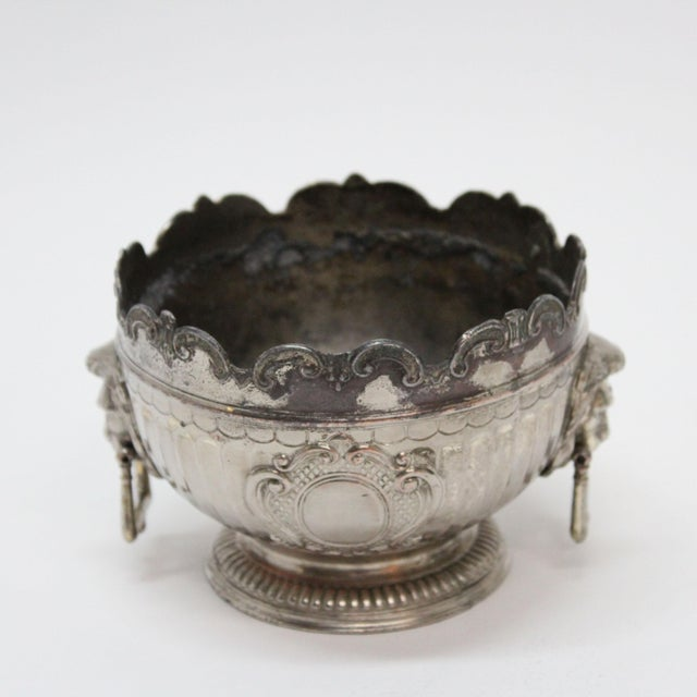 This is a vintage silver-plated bowl with lion head handles as made by Corbell and Company. The bowl is edged with a...