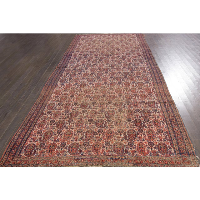Vintage, hand-knotted Persian rug with an allover burgundy design on an ivory field.