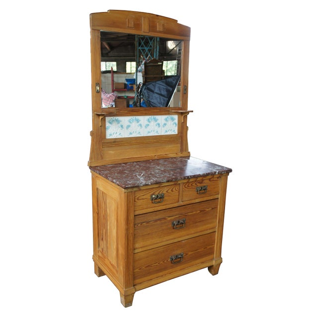 Turn of the century solid pine marble top washstand with tiled and mirrored back. Features 4 hand dovetailed drawers and...