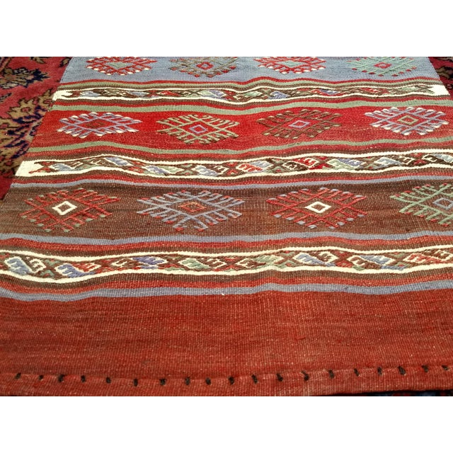 A beautiful Moroccan Kilim runner in stripes design with vibrant colors in red, green, purple, orange, blue. In addition,...