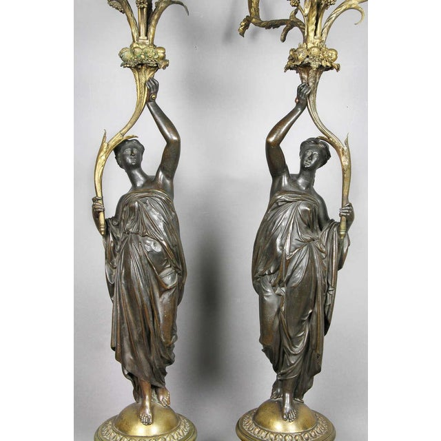 Patinated bronze female figures supporting three candle arms, raised on circular red marble section with square bases with...