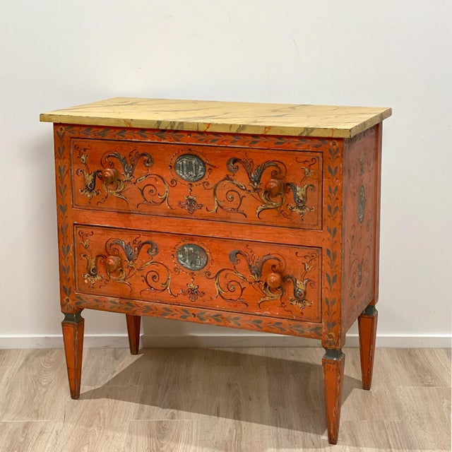A 19th Century Italian painted chest of drawers with a faux marble top, later paint