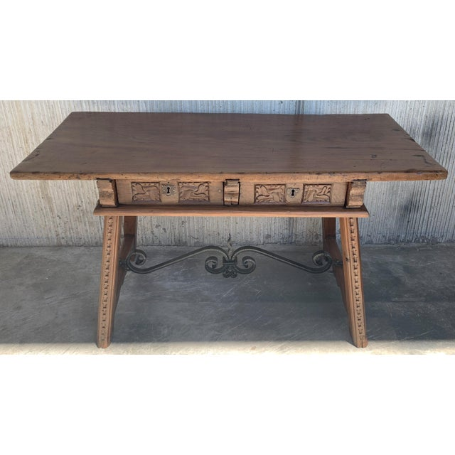 About A Spanish Baroque style walnut table from the early 18th century, with two drawers, caved legs and iron hardware....