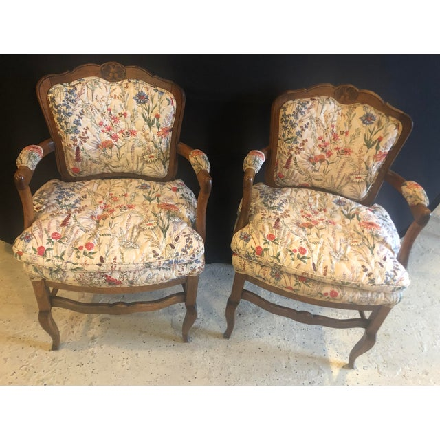 An elegant pair of country French boudoir Louis XI style fauteuils or armchairs. The chairs feature a hand-quilted...
