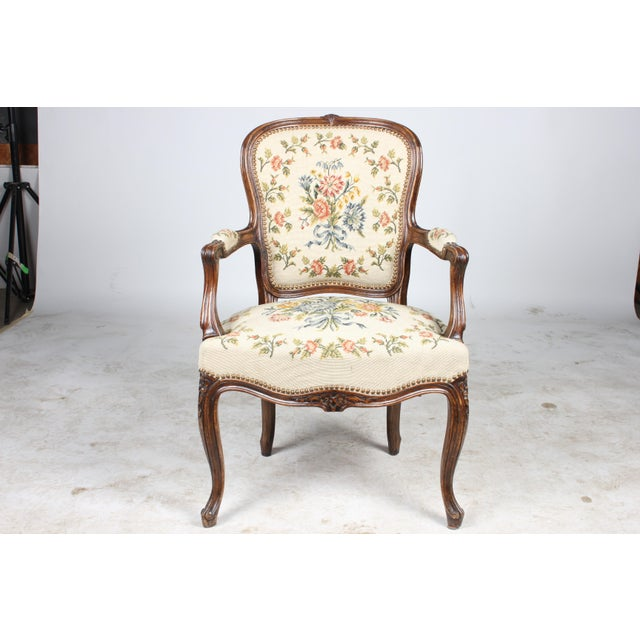 1930s Louis XVI-style fauteuil chair featuring lovely needlepoint on back and seat of chair, colors are cream, pink, red,...