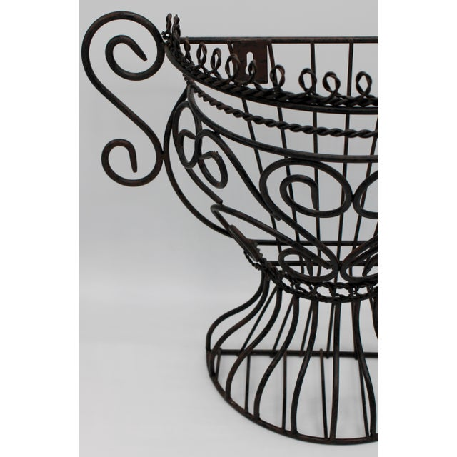 A superb French black metal garden wall jardiniere. Urn-shaped with lovely curled handles and ornate design. Ready to hang!