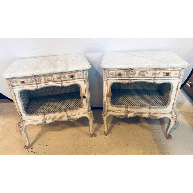 A Distressed Pair of Marble Top End Tables or Bed/Night side Stand. These wonderfully decorative parcel paint and gilt...
