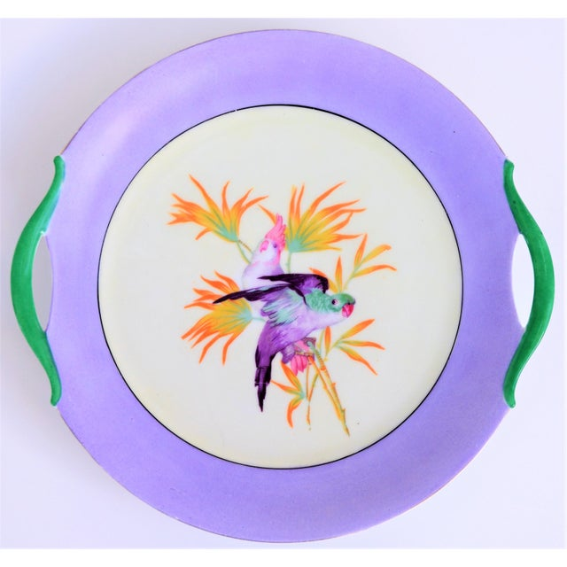 """This is a beautiful cake plate. This plate is about of 10"""" in diameter and has a pretty lilac border with two cockatiel in..."""