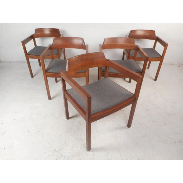 This beautiful set of five vintage modern dining chairs feature a solid walnut frame with arm rests and an upholstered...