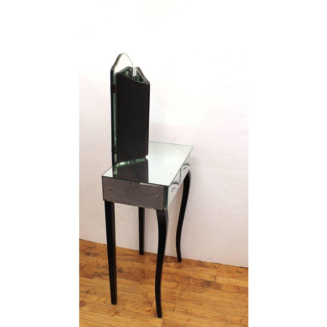 Art Deco vanity with trifold mirror produced in France during the 1930s. The table features a mirrored surface including...