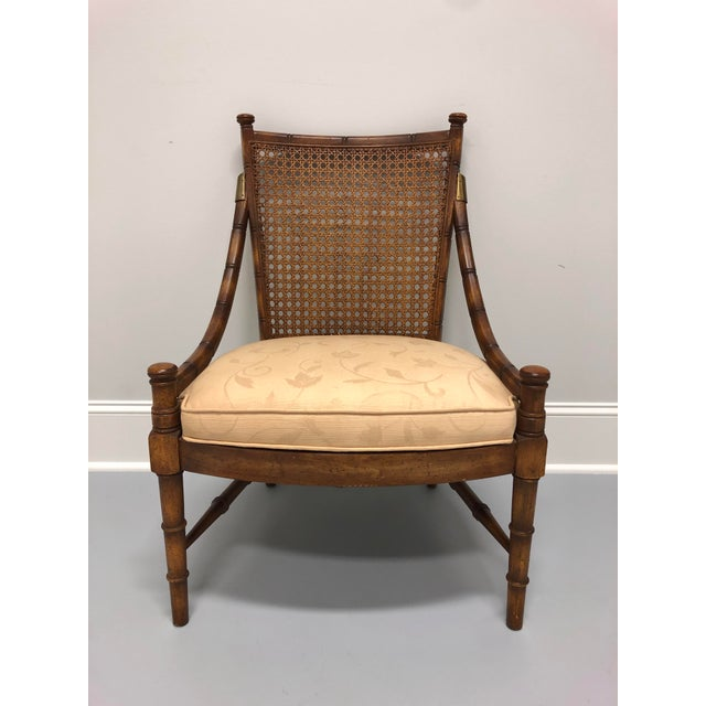 A low lounge chair in faux bamboo with caned seatback and brass accents. Made in the USA in the mid 20th Century. Overall:...