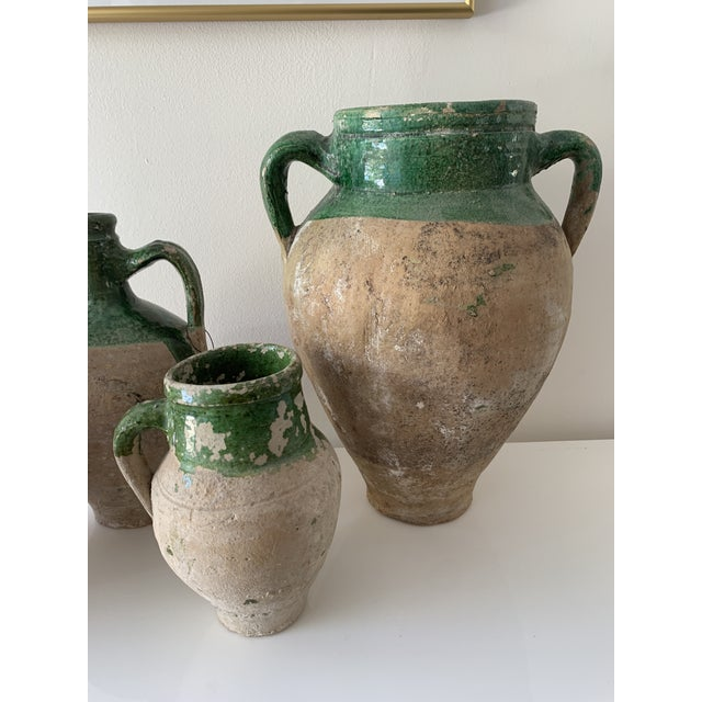 French earthenware confit pots and amphora with traditional green glaze. Some chips and losses to glaze. These ordinary...