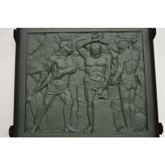 Rare antique cast iron fireback depicting Foundry Workers. Item features heavy cast iron construction, three impressive...
