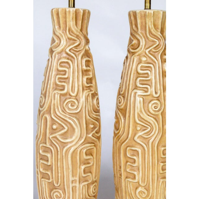 A pair of Mid-Century, American pottery lamps carved with high relief designs reminiscent of South American geoglyphs....