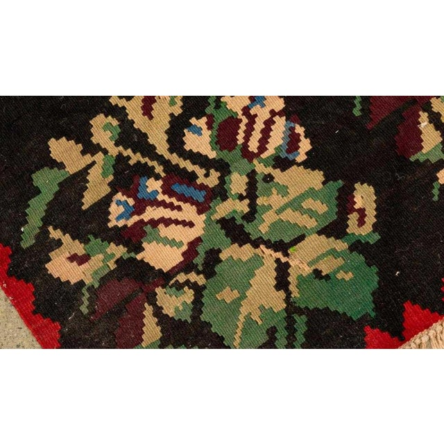 Kilim style rug in vibrant red, blues and greens. Likely a cotton/wool blend.