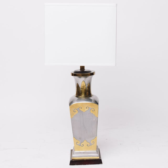 This vintage lamp has an elegant slate/gray metallic silver finish accented with brass detailing. It's a strong Hollywood...