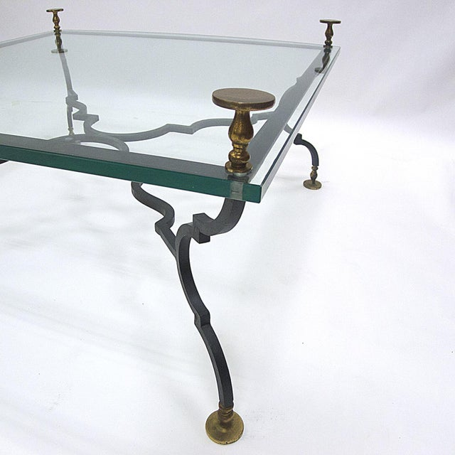Very heavy decorative wrought iron and glass table with solid brass feet and finials. This table is stunning! Unique...