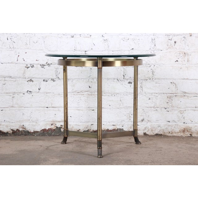 A gorgeous midcentury Hollywood Regency brass and glass side table by Labarge. The table features a stylish three-legged...