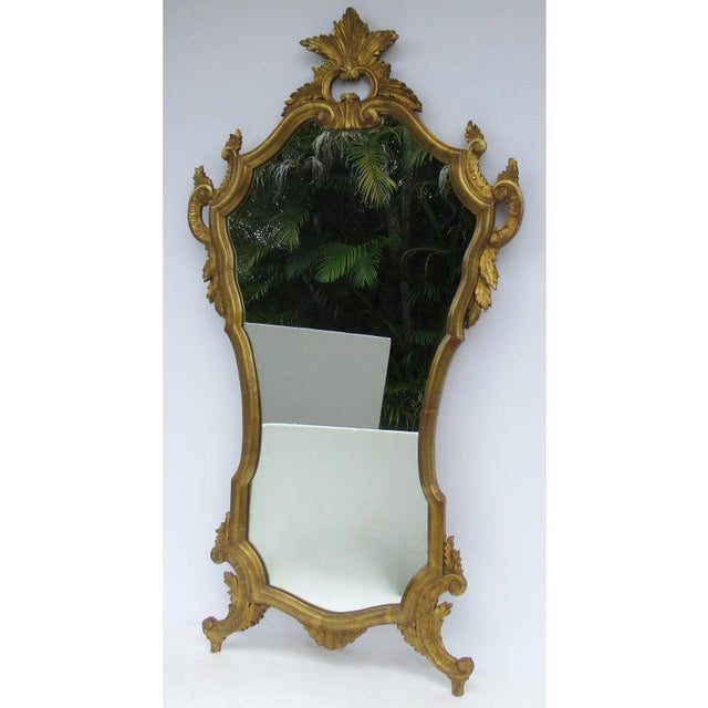 Vintage: 1950's, Hollywood Regency Era, Italian Venetian, gilt gold leaf carved wall mirror. A sinuous, famine, linear and...