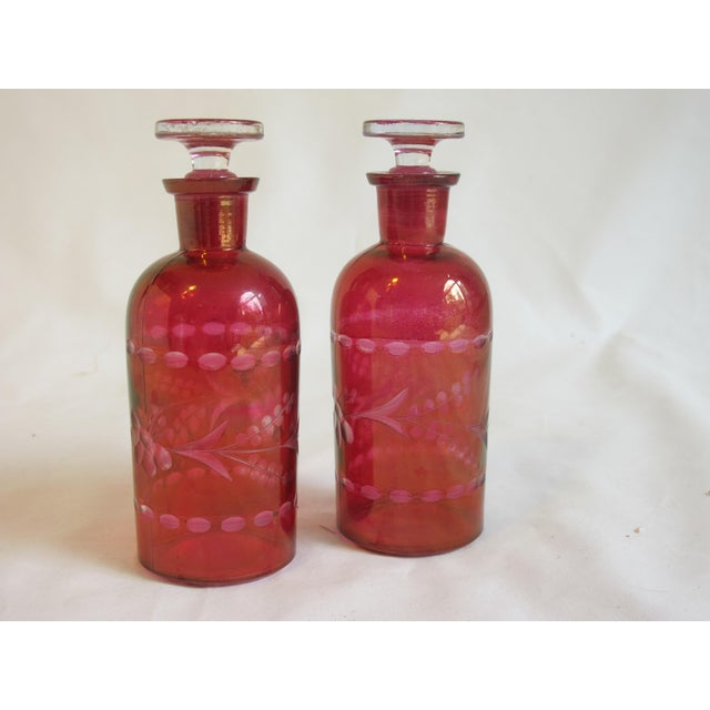 A pair of cranberry red bohemian cut class stopper top bottles,