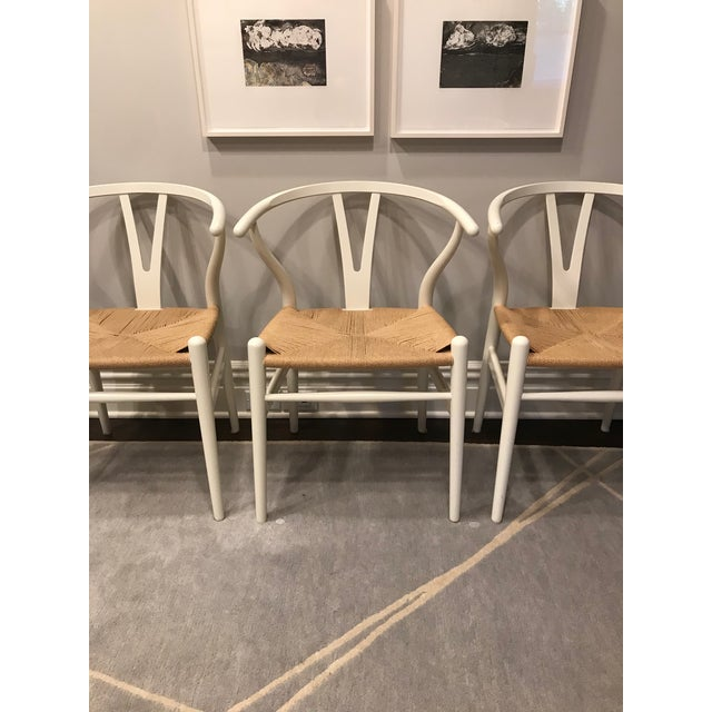 6 Hans Wegner Wishbone Chairs, purchased at Design Within Reach for a dining area. The wood is white and the woven seats...
