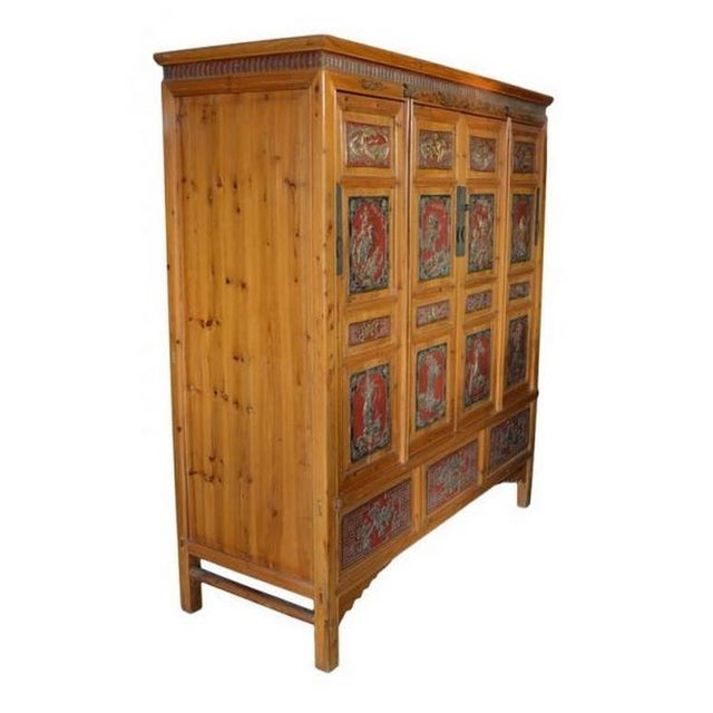 This Chinese 19th century antique wide and large cabinet showcases hand-carved and gilded wooden panels. This impressive...