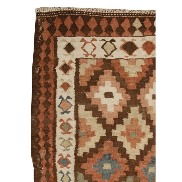 An early 20th century Persian Shahsavan Kilim runner with an all-over multicolored diamond pattern surrounded by multiple...