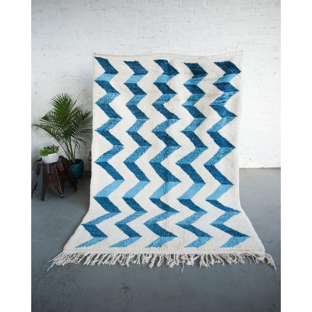 "Hand-knotted Berber wool rug with light blue and dark blue zig-zag pattern over a natural wool base. 100% wool. 3/4"" Pile..."
