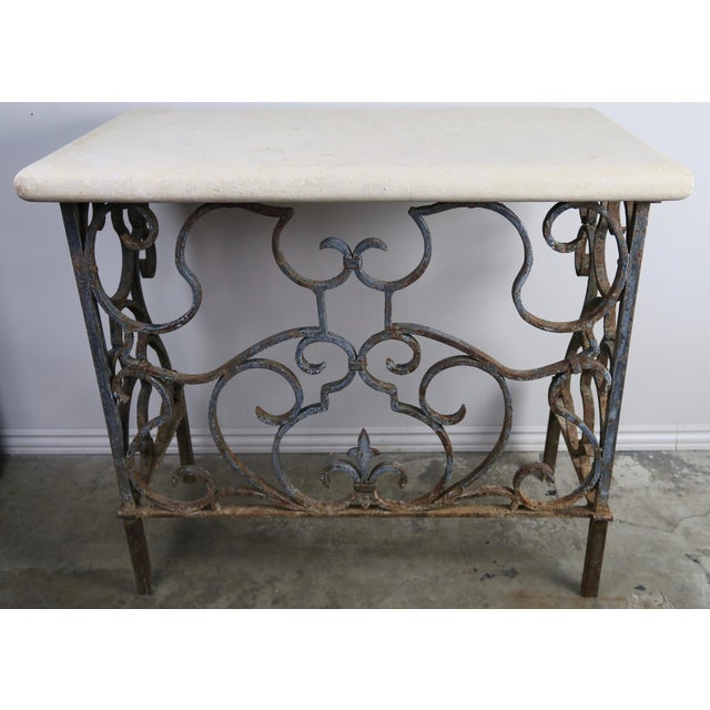 French Hand wrought iron console base with Fleur di Lys. The console supports a travertine top. Beautiful distressed...