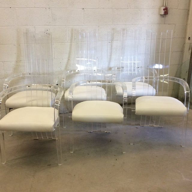 Fabulous set of six heavy, thick lucite dining chairs. All with arms and newly reupholstered in white recycled grain...