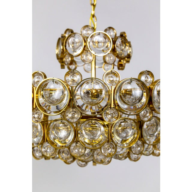 A Mid Century Modern Palwa chandelier with a complex, multi tier design with 11 lights; a gilded brass, circular structure...