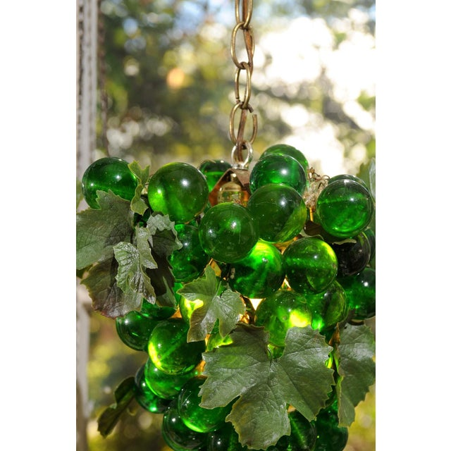 Vintage iconic grape cluster swag light made of lucite orbs, vinyl leaves, and the original vintage brass chain of 11' in...