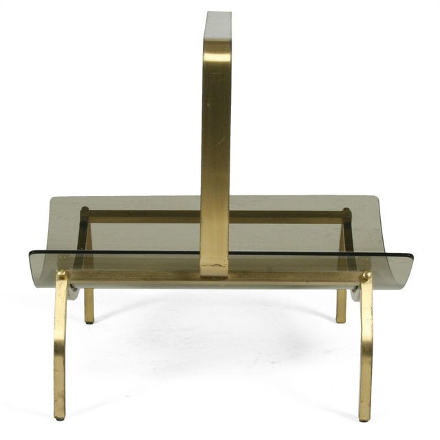 A chic magazine stand comprising a curved smoked glass shelf held within a bronze frame with an integral handle. By...