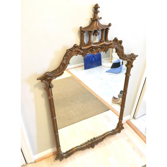 Ornately carved gilt wood chinoiserie style mirror. Beautiful pagoda and bell adorn the top.