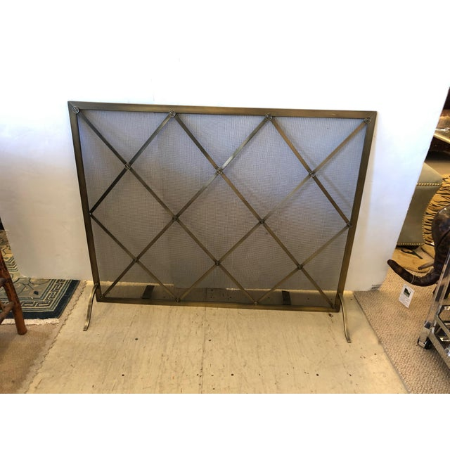 Beautiful brass and iron mesh mid-century modern fireplace screen in bronzey gold color, having the criss cross pattern in...