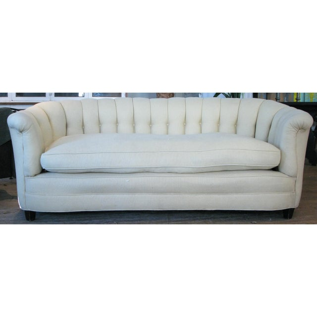 A charming vintage 1940s curved sofa with channel upholstery and button tufting, and with its original down feather seat...