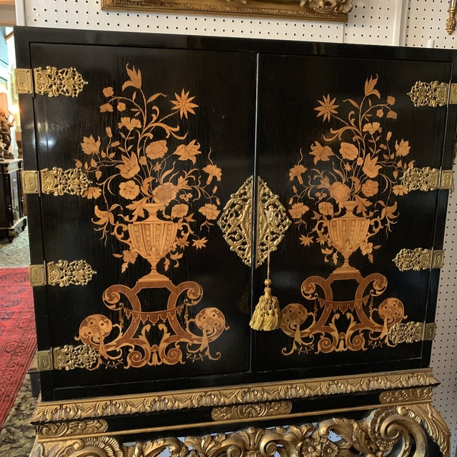 Beautiful early to mid 20th century English black lacquered gilt painted marquetry inlaid cabinet on stand. Two fitted...