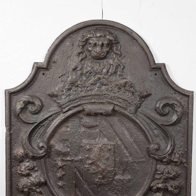 This stately antique fireback features an arch top scalloped top with a lion's head in relief above a crest that is...