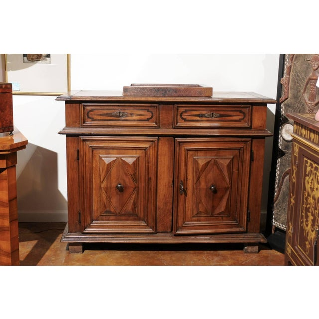 An Italian walnut two-door buffet from the 19th century, with raised diamond motifs and banded inlay. This Italian walnut...