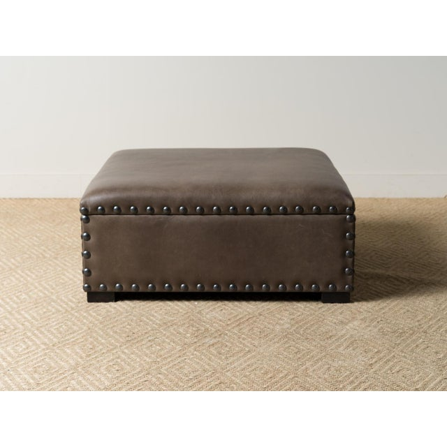 Custom upholstered ottoman with hinged lid. Interior coated interior for storage. Block feet and jumbo nailhead trimming....